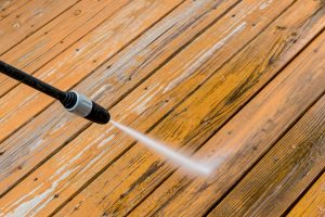 power washing. wooden deck floor cleaning with high pressure water jet.